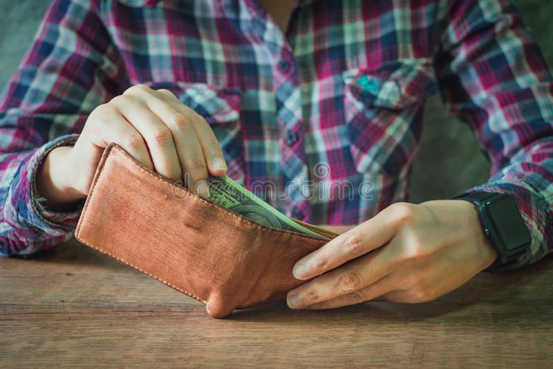 Sluit omhoog van handen houdend het bruine hoogtepunt van de leerportefeuille van geld stock afbeelding