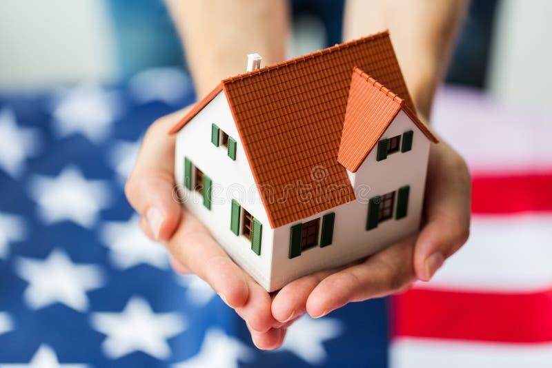 Sluit omhoog van handen houdend huis over Amerikaanse vlag stock fotografie
