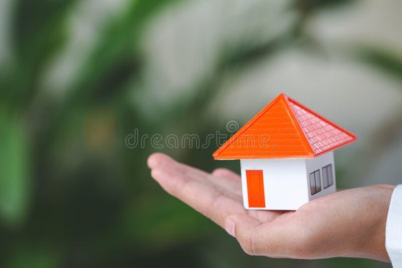 Sluit omhoog van handen houdend huismodel, bouw, hypotheek, en bezitsconcept de onroerende goederen stock fotografie