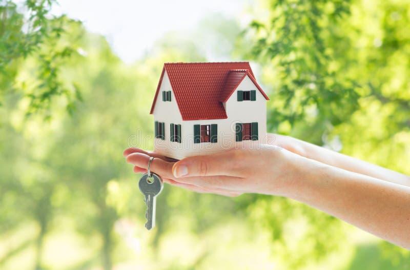 Sluit omhoog van handen houdend huismodel en sleutels stock afbeelding