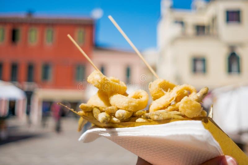 Sluit omhoog van handen houdend straatvoedsel bestaand uit gebraden vissen binnen een document kegel in Venetië tijdens zonnige d royalty-vrije stock foto