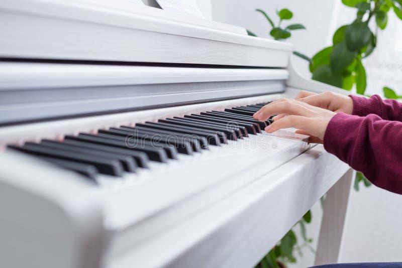 Sluit omhoog van handen van jonge meisje het spelen piano royalty-vrije stock foto's