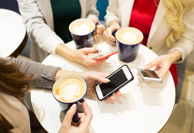 Sluit omhoog van handen met koffiekoppen en smartphones stock afbeeldingen