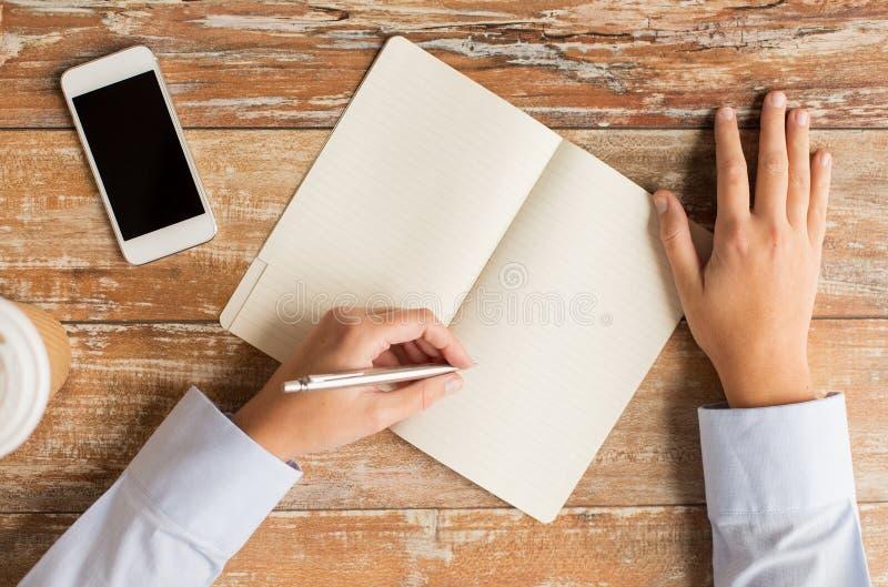 Sluit omhoog van handen met notitieboekje en smartphone stock afbeeldingen