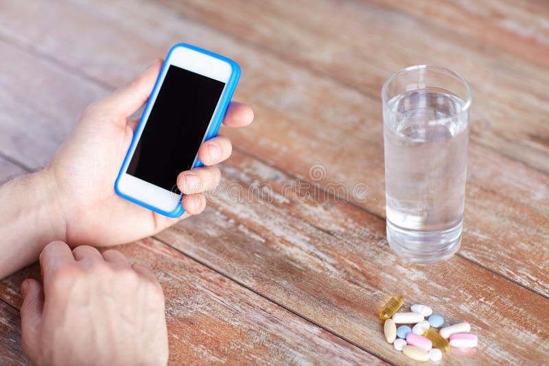 Sluit omhoog van handen met smartphone, pillen en water royalty-vrije stock fotografie