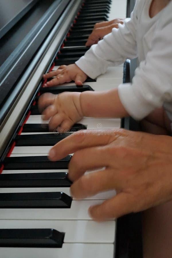 Sluit omhoog van handen op toetsenbord het spelen piano, kind met grootmoeder stock afbeeldingen