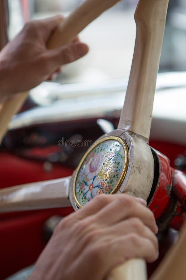 Sluit omhoog van handen van een mens die het stuurwiel van een vinta houdt stock foto