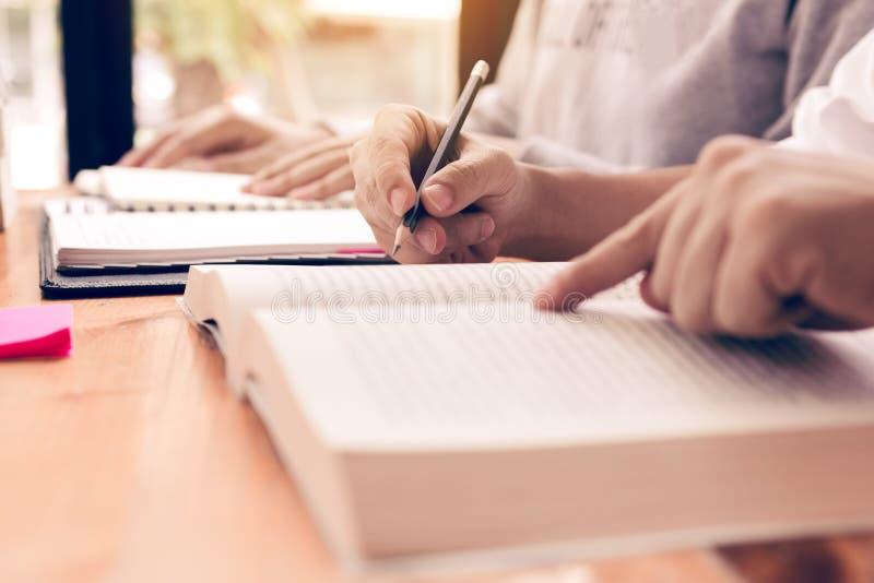 Sluit omhoog van handentiener het schrijven op notitieboekje en vrienden die een boek in bibliotheekacademie lezen royalty-vrije stock fotografie