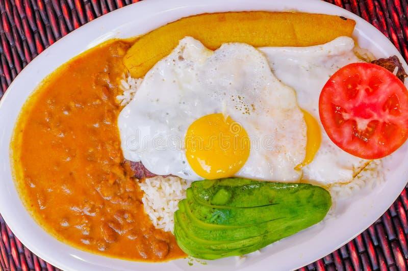 Sluit omhoog van heerlijk Ecuatoriaans die voedsel, rijst, eieren, pplantains, avocadotomaat in een witte plaat over houten wordt stock fotografie