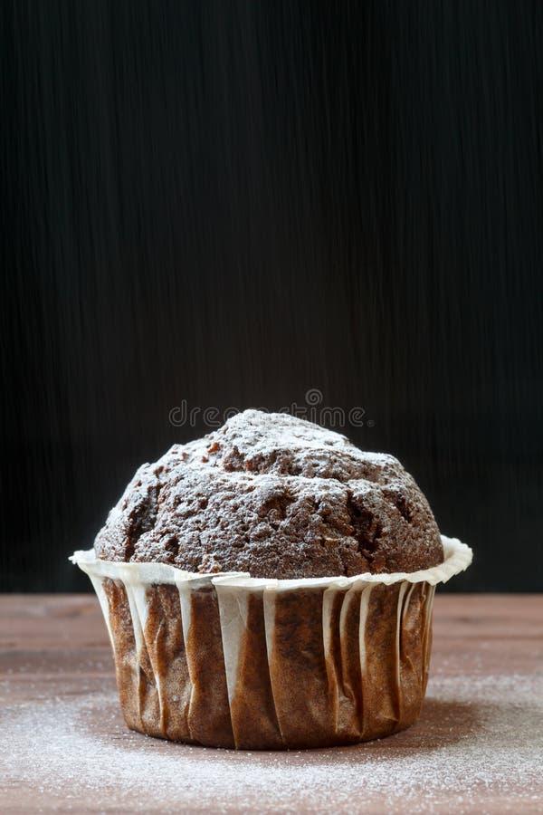 Sluit omhoog van heerlijke chocolademuffin op een houten lijst, tegen zwarte die achtergrond, met sneeuw zoals poedersuiker rond  stock afbeeldingen