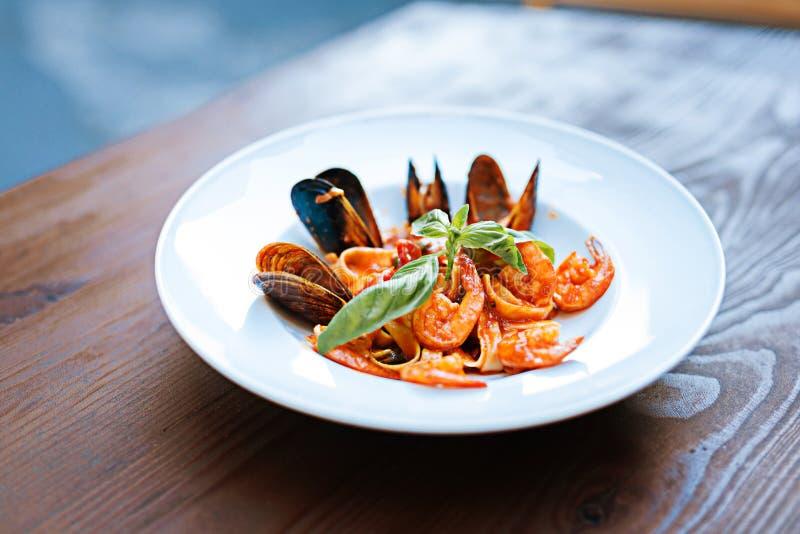 Sluit omhoog van heerlijke deegwaren met wat zeevruchten in tomatensaus stock fotografie