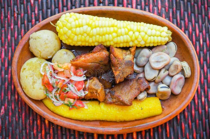 Sluit omhoog van heerlijke hornado, Ecuatoriaans traditioneel typisch Andesdievoedsel met graan, aardappel, salade, weegbree word royalty-vrije stock afbeeldingen