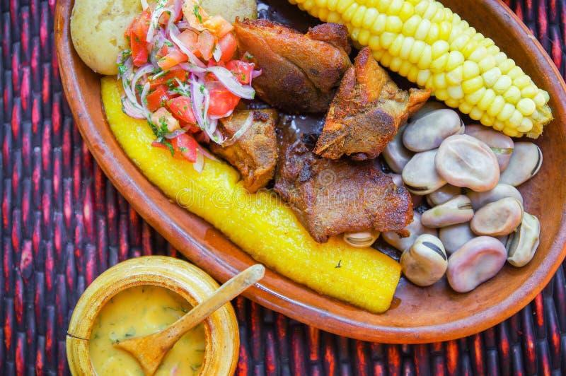 Sluit omhoog van heerlijke hornado, Ecuatoriaans traditioneel typisch Andesdievoedsel met graan, aardappel, salade, weegbree word stock fotografie