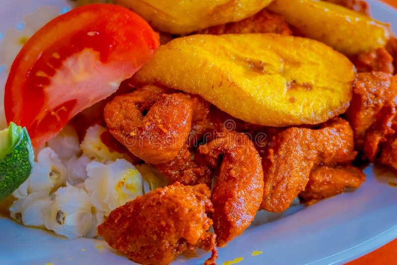 Sluit omhoog van heerlijke hornado, Ecuatoriaans traditioneel typisch Andesdievoedsel met graan, aardappel, zoete weegbree wordt  stock foto