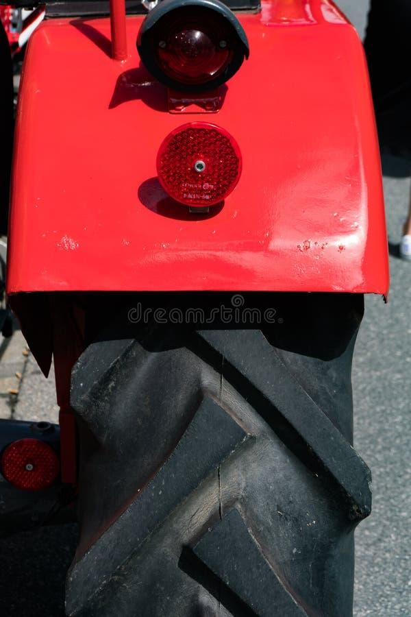 Sluit omhoog van het achterwiel en het stootkussen van een klassieke rode tractor stock fotografie