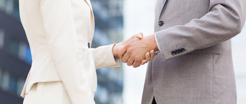 Sluit omhoog van het bedrijfspaar schudden handen stock foto