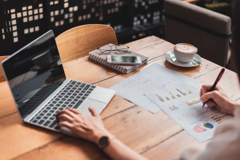 Sluit omhoog van het bedrijfsvrouw werken met documenten en laptop in bureau Zaken en Levensstijlenconcept Ondernemer en stock afbeelding