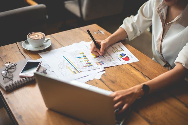 Sluit omhoog van het bedrijfsvrouw werken met documenten en laptop in bureau Zaken en Levensstijlenconcept Ondernemer en stock foto's