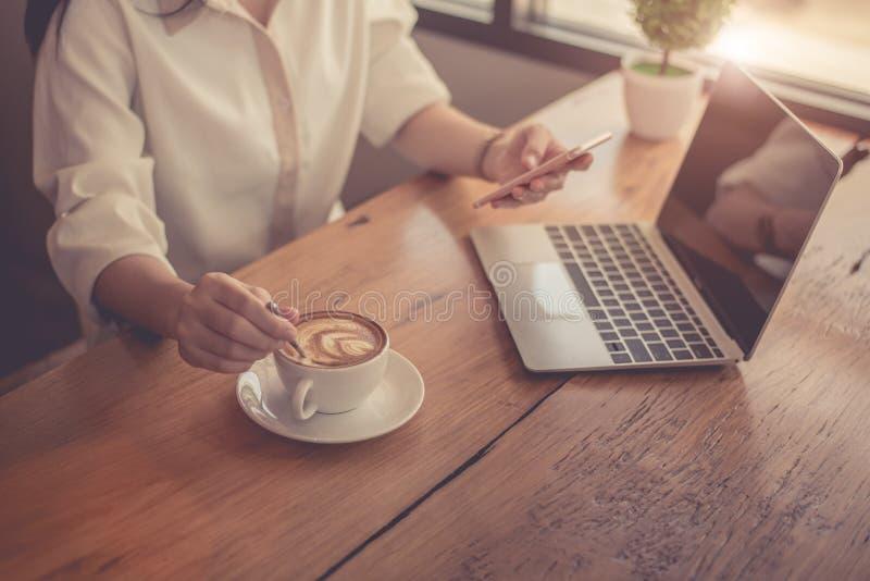Sluit omhoog van het bedrijfsvrouw werken met laptop en het drinken koffie in bureau Zaken en Levensstijlenconcept Ondernemer en stock fotografie