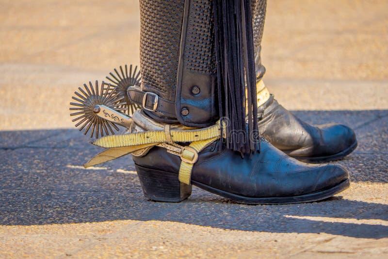 Sluit omhoog van het berijden van aansporingen met scherp arenspoorradje op de authentieke westelijke laarzen van het cowboy trad stock afbeeldingen