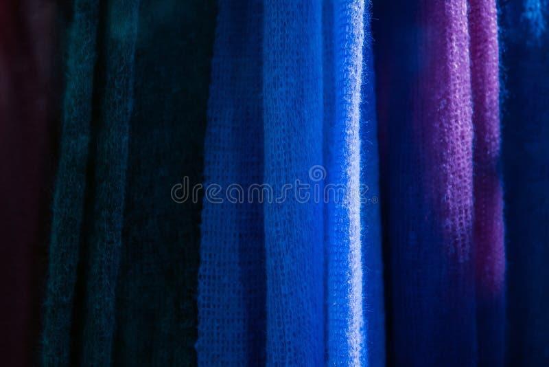 Sluit omhoog van het breien textuur Gebreide kleurrijke stoffen bij de kledingsopslag stock foto's