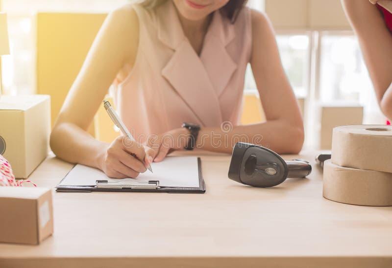 Sluit omhoog van het de eigenaarwerk van de handvrouw aangaande bureau, Kleine onderneming, de online zaken van het MKB en Beginu stock afbeeldingen