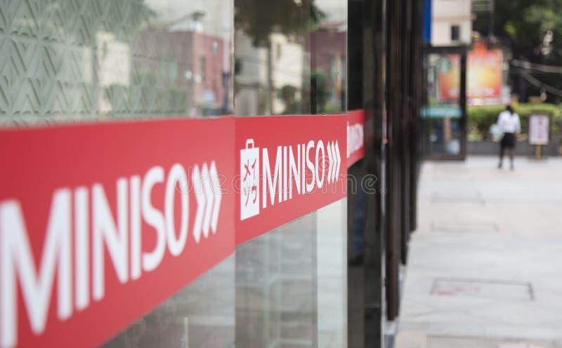 Sluit omhoog van het embleem van Miniso voor een opslag stock fotografie