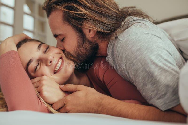 Sluit omhoog van het gelukkige paar romancing in bed stock afbeelding