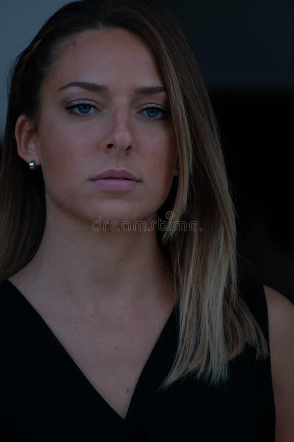 Sluit omhoog van het gezicht van een zeer leuk blondemeisje met blauwe ogen, met zwarte kleding Zeer expressief en ernstig gezich stock foto