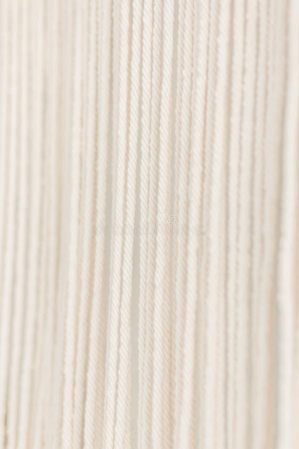 Sluit omhoog van van het katoenen het garen macramépaneel in een minimalistic Skandinavische muur Textuur Achtergrond royalty-vrije stock fotografie