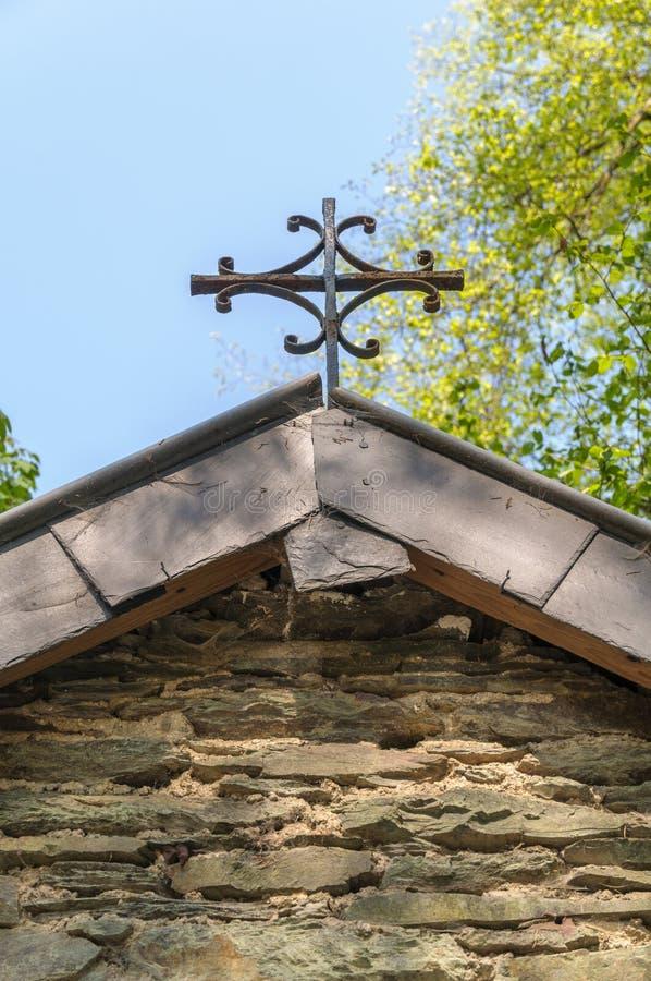 Sluit omhoog van het kruis bovenop het dak van een kleine kapel in de Ardennen, België stock afbeeldingen