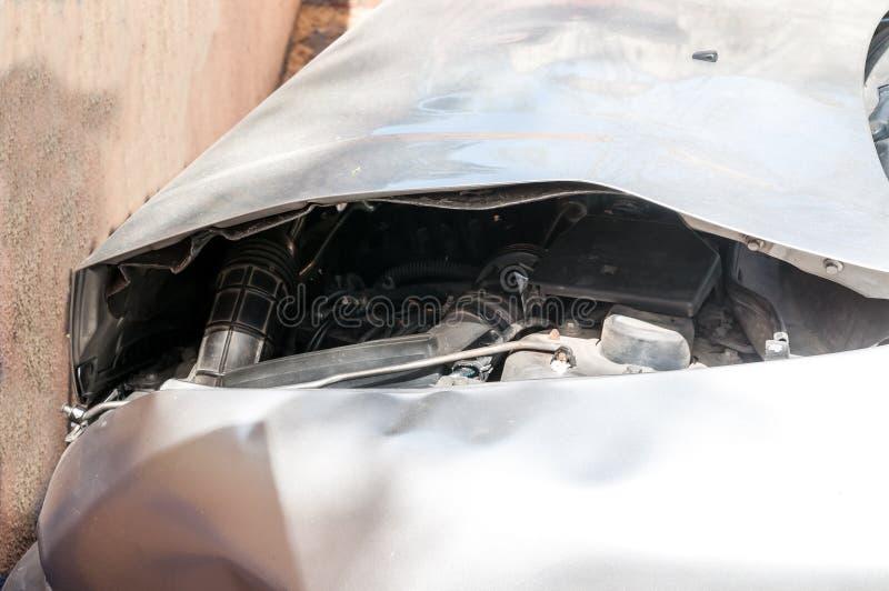 Sluit omhoog van het ongeval van de autoneerstorting met beschadigd voordieeind binnen aan de muur wordt verpletterd royalty-vrije stock foto's