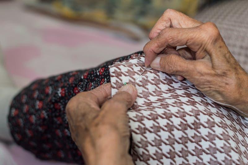 Sluit omhoog van het oude hogere vrouwenhanden naaien stock foto's