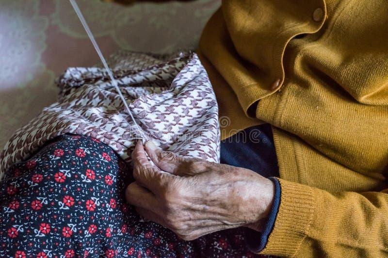 Sluit omhoog van het oude hogere vrouwenhanden naaien royalty-vrije stock fotografie