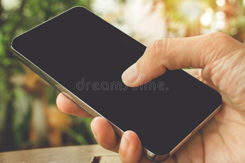 Sluit omhoog van het raken van handen houdend ruimte van het telefoon de zwarte exemplaar met zonsondergangachtergrond royalty-vrije stock fotografie