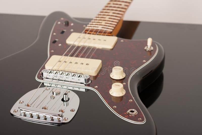 Sluit omhoog van het staartstuk van de chroomtremolo en outputschakelaar op zwarte elektrische gitaar royalty-vrije stock foto