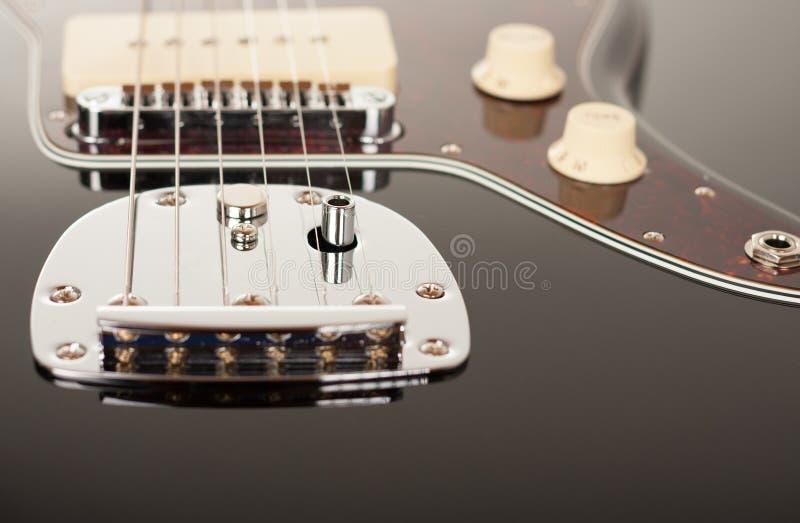 Sluit omhoog van het staartstuk van de chroomtremolo op zwarte elektrische gitaar, studiospruit Rode schildpadshell pickguard royalty-vrije stock afbeeldingen