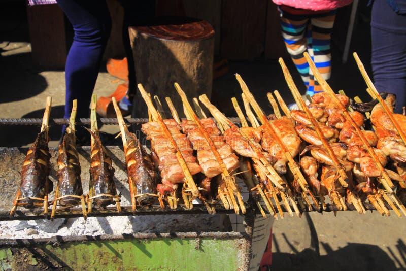 Sluit omhoog van het traditionele voedsel van de barbecuestraat met vissen en kippendarmen op vleespennen over houtskoolgrill - V royalty-vrije stock afbeelding