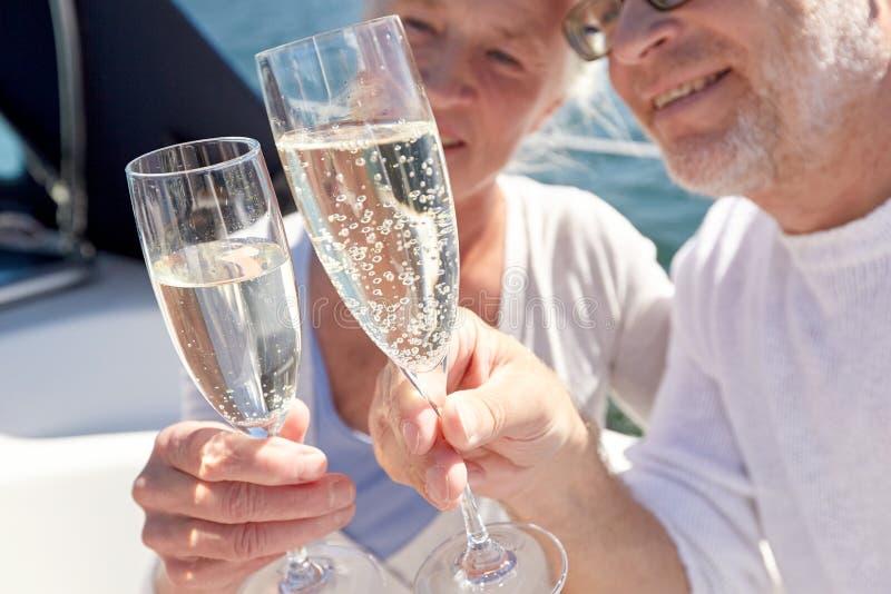 Sluit omhoog van hoger paar met champagne op boot stock afbeelding