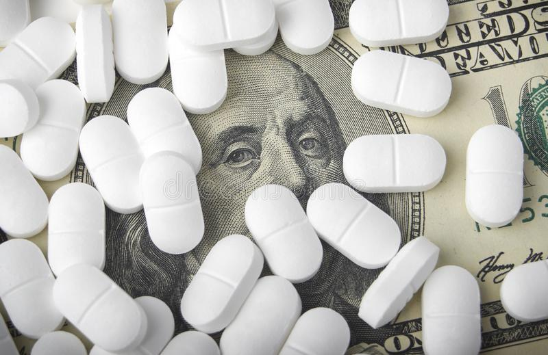 Sluit omhoog van honderd dollarrekening met pillen stock foto's