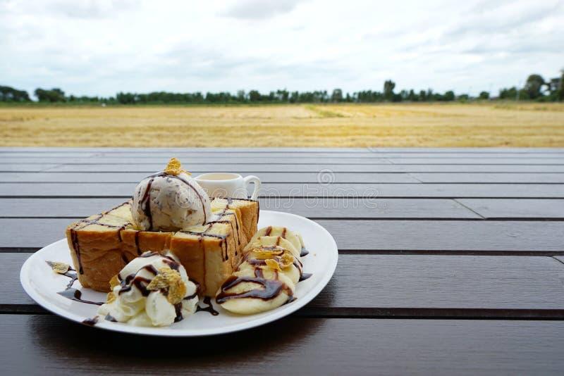 Sluit omhoog van honingstoost met roomijs, chocolade, ransel room en graangewas met honing op de houten lijst wordt bedekt die royalty-vrije stock foto