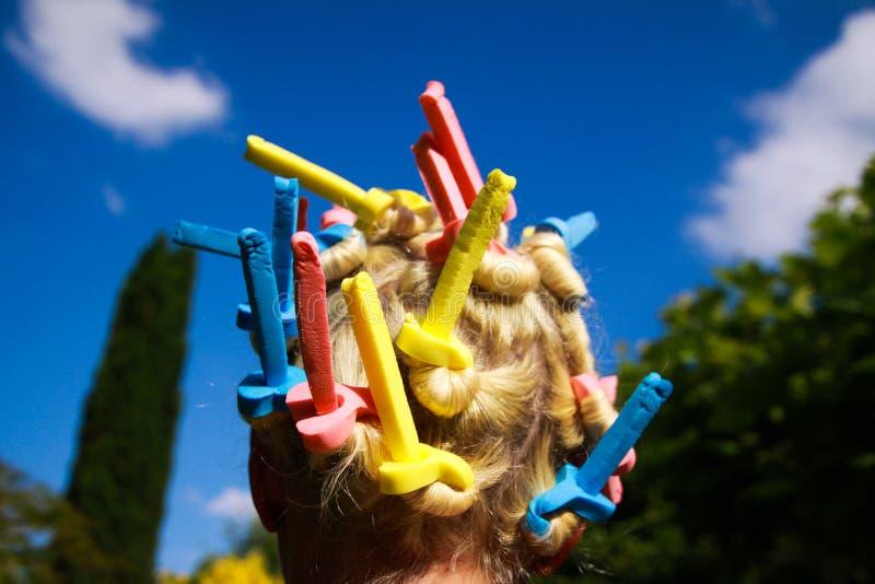 Sluit omhoog van hoofd van Europese vrouw met blondehaar en kleurrijke ouderwetse schuimkrulspelden stock foto's