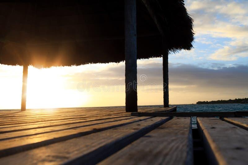 Sluit omhoog van houten gazebo op het strand bij zonsondergang of zonsopgang Achtergrond van een kust met palmen en blauw water i stock foto