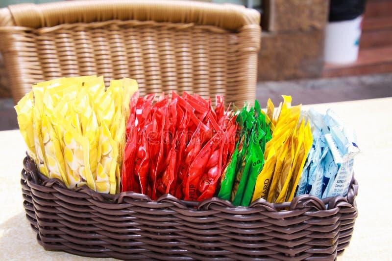 Sluit omhoog van houten mand met keus van kleine kleurrijke plastic pakketten van sausen op lijst van restaurant openlucht royalty-vrije stock foto