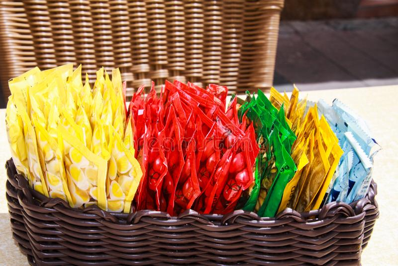 Sluit omhoog van houten mand met keus van kleine kleurrijke plastic pakketten van sausen op lijst van restaurant openlucht royalty-vrije stock afbeelding