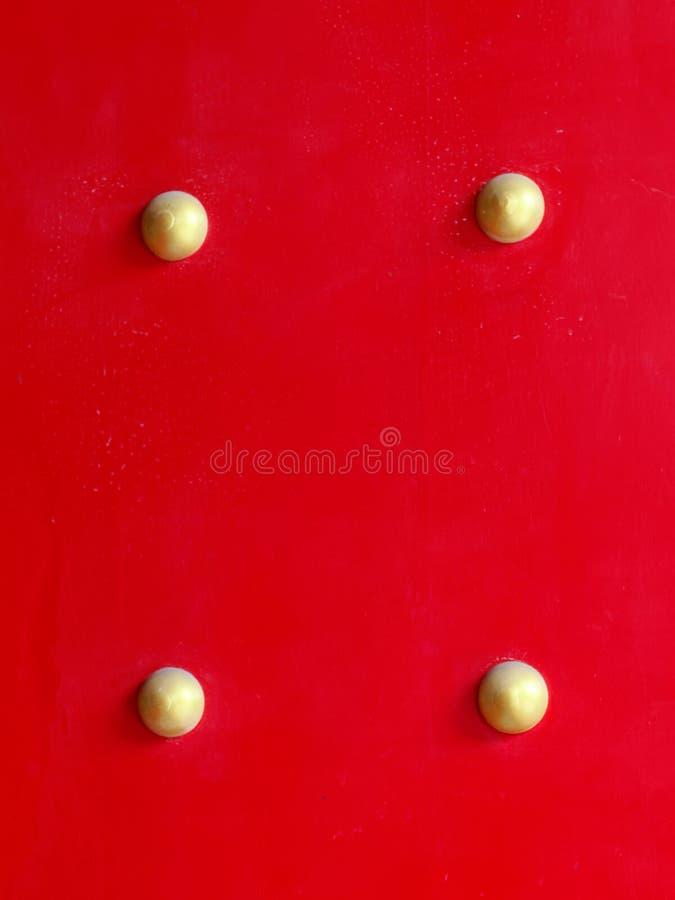 Sluit omhoog van houten rode poort of deur met gouden klinknagel of knoop van Chinese heiligdom of tempel stock foto