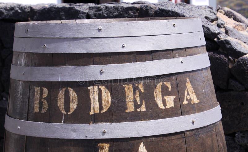 Sluit omhoog van houten wijnvat met tekst Bodega voor natuursteenmuur - Lanzarote stock afbeelding