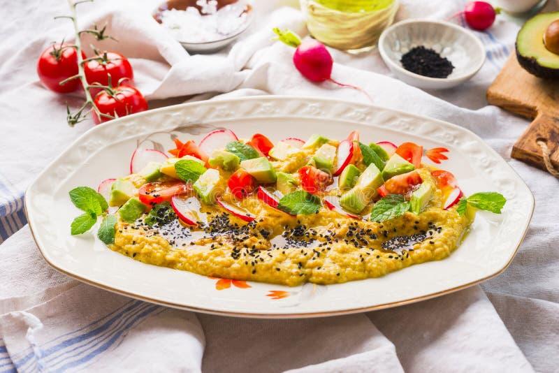 Sluit omhoog van hummusplaat met olijfolie, avocado, verse die groenten en kruiden wordt bedekt op keukenlijst wordt gediend, hoo royalty-vrije stock afbeelding