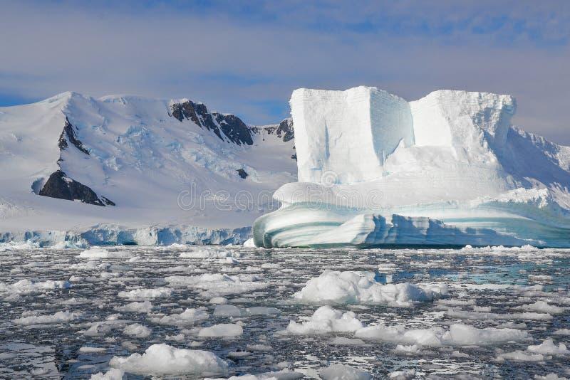 Sluit omhoog van ijsberg door water wordt door smeltend ijs wordt omringd gevormd dat royalty-vrije stock fotografie