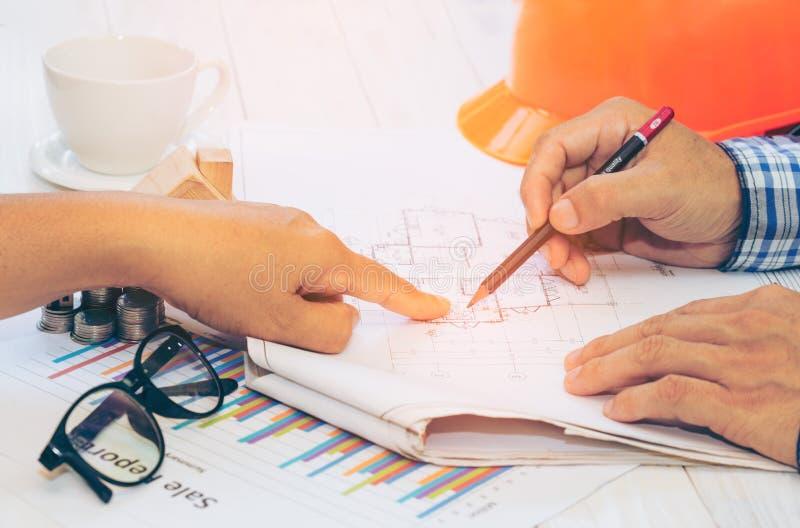 Sluit omhoog van ingenieurshanden besprekend een bouwconstructieproject op het werk bedrijfsfinanciën, blauwdrukken, stock foto's